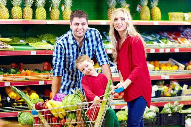 Mother and father shopping with their son in a produce aisle