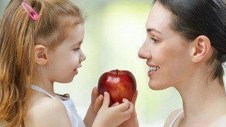 A mother hands her daughter a red apple