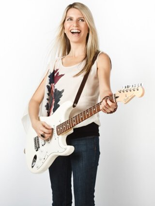 Alicia Grant plays guitar while standing