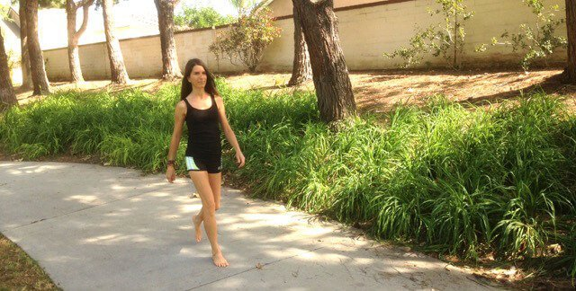 Alicia Grant walks barefoot outside along a sidewalk