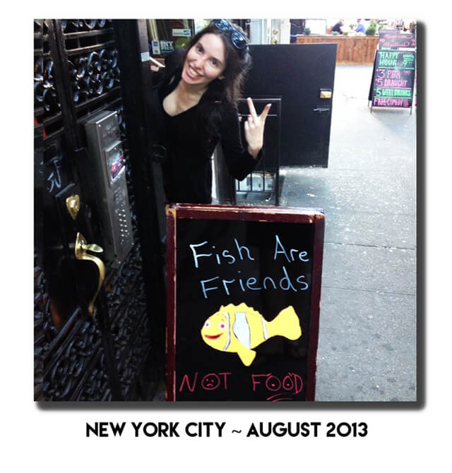 "Jenny Lapan gives a peace sign behind a ""Fish Are Friends"" sign in New York City"