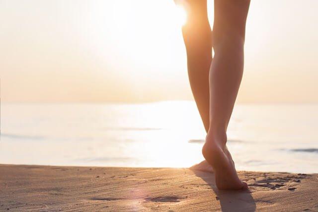 A woman walks on a beach
