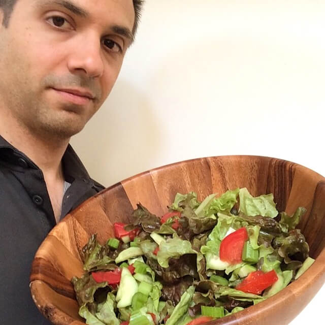 John Fallucca holding a bowl filled with salad