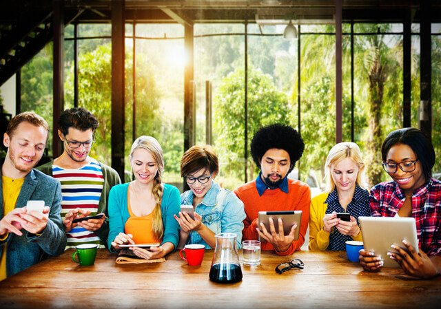 Seven people absorbed with technology and not speaking to one another