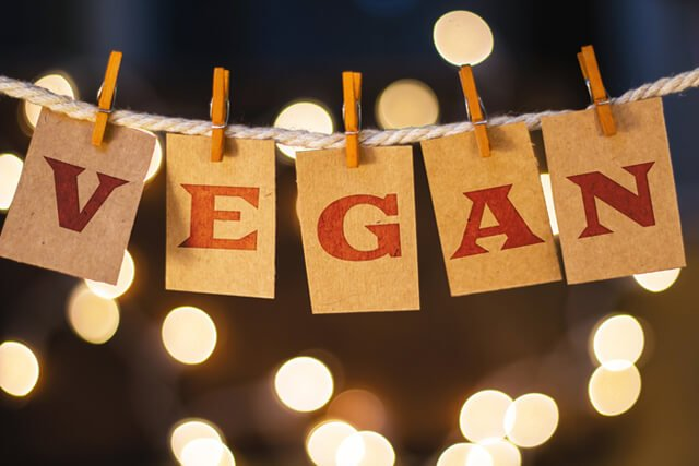 "The word ""vegan"" printed on clothespin-clipped cards in front of defocused glowing lights"