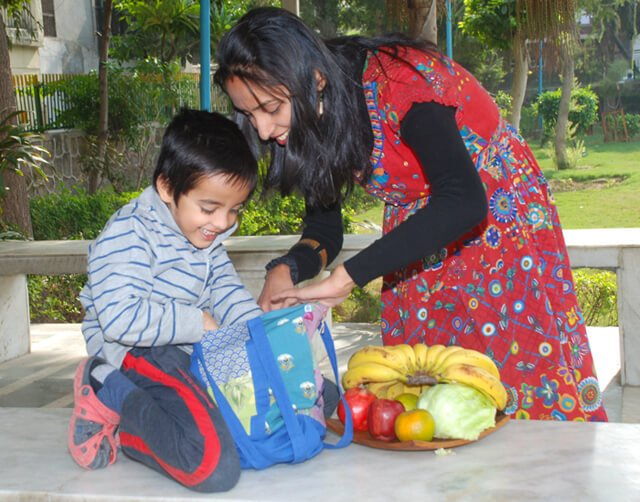Anjali and Manikya Sanghi pack bags with fruit
