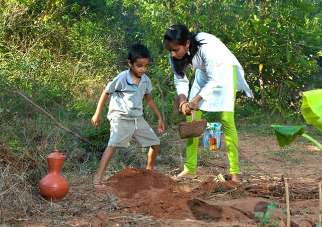 Anjali and Manikya Sanghi stand while planting fruit trees