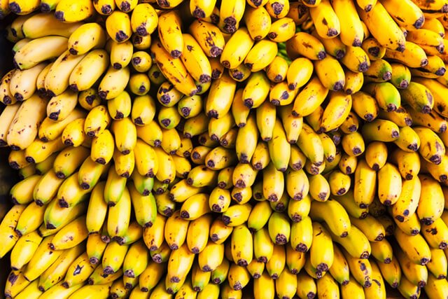 Dozens of bananas are stacked at a market