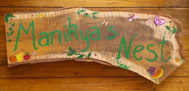 """Manikya's Nest"" is painted on a piece of wood."