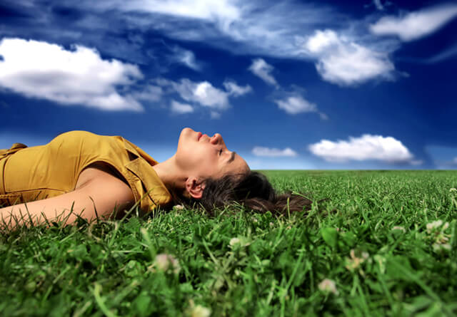 A woman takes in sunshine while laying on grass