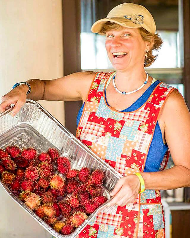 Itsy Sweeney holds a tray of rambutans