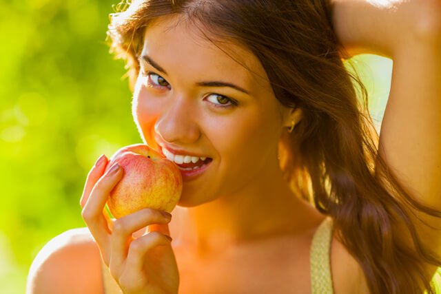 Woman enjoys an apple outside
