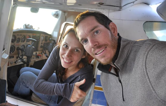 Korey Constable poses with Deanna Husk, seated in a cockpit