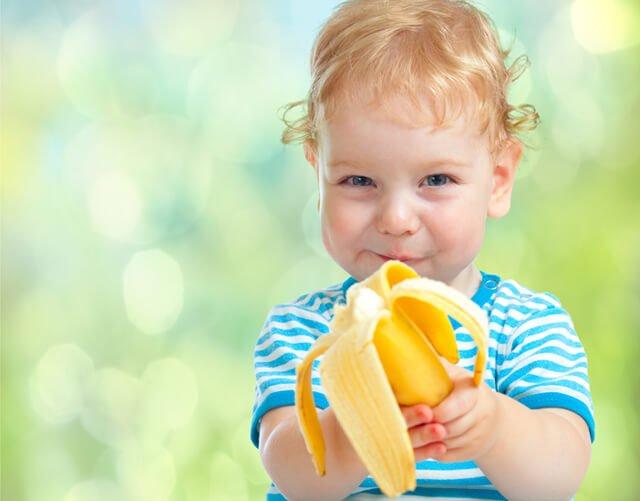 A male toddler eats a banana