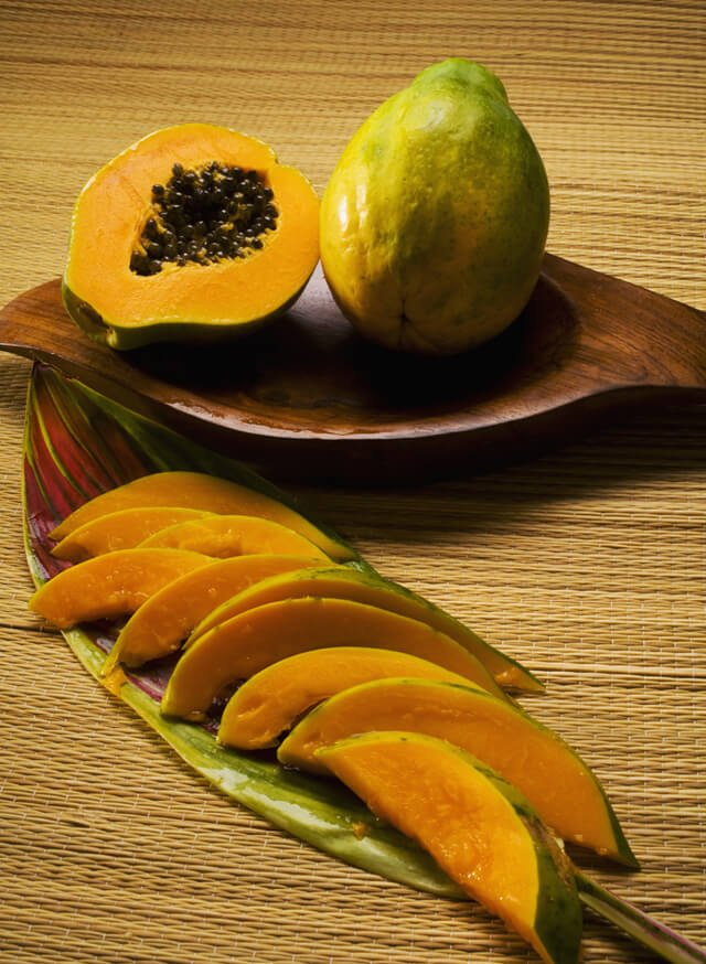 Hawaiian papaya halved and sliced on a plate
