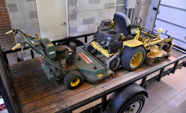 Two lawnmowers are stationed on a trailer