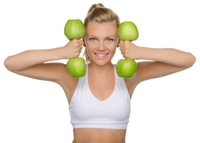 Woman with dumbbells of green apples
